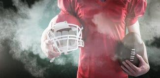 Immagine composita del giocatore di football americano che tiene un casco e una palla Immagini Stock