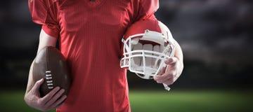 Immagine composita del giocatore di football americano che tiene un casco e una palla Fotografia Stock Libera da Diritti