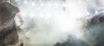 Immagine composita del giocatore di rugby che tiene la palla Immagini Stock