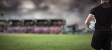 Immagine composita del giocatore di rugby che tiene la palla Fotografia Stock