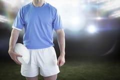 Immagine composita del giocatore di rugby che tiene una palla di rugby Fotografia Stock