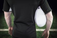 Immagine composita del giocatore di rugby che tiene una palla di rugby Immagine Stock