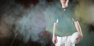 Immagine composita del giocatore di rugby che tiene una palla di rugby Immagini Stock Libere da Diritti
