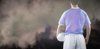 Immagine composita del giocatore di rugby che tiene una palla di rugby Immagini Stock