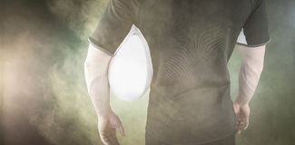 Immagine composita del giocatore di rugby che tiene una palla di rugby Fotografie Stock