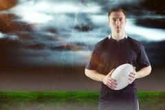 Immagine composita del giocatore di rugby che tiene una palla di rugby 3D Fotografia Stock