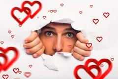 Immagine composita del giovane che guarda attraverso lo strappo di carta Fotografie Stock