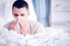 Immagine composita del giovane che soffia il suo naso fotografie stock