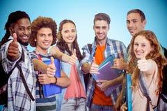 Immagine composita del gruppo sorridente di studenti che fanno i pollici su Fotografia Stock