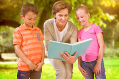 Immagine composita del libro di lettura dell'insegnante con gli allievi alla biblioteca Immagini Stock Libere da Diritti