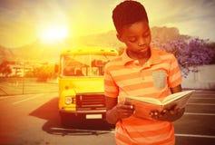 Immagine composita del libro di lettura sveglio del ragazzo in biblioteca Immagini Stock