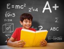 Immagine composita del libro di lettura sveglio del ragazzo in biblioteca Immagini Stock Libere da Diritti
