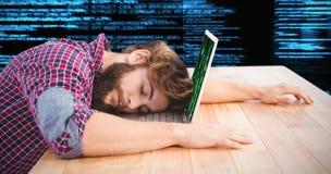 Immagine composita del pisolino dei pantaloni a vita bassa con la testa sul computer portatile Fotografia Stock