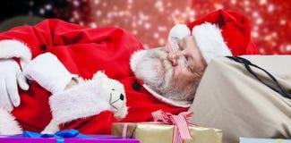 Immagine composita del primo piano del Babbo Natale stanco che dorme accanto ai regali di Natale Immagine Stock