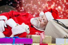 Immagine composita del primo piano del Babbo Natale stanco che dorme accanto ai regali di Natale Fotografie Stock