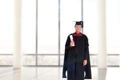 Immagine composita del ragazzo laureato affascinante con il suo diploma Fotografia Stock Libera da Diritti