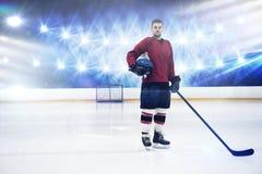 Immagine composita del ritratto del casco e del bastone della tenuta del giocatore di hockey su ghiaccio fotografia stock