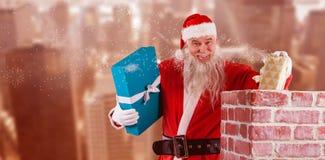 Immagine composita del ritratto del Babbo Natale che dispone i contenitori di regalo nel camino Fotografie Stock Libere da Diritti