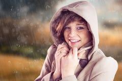 Immagine composita del ritratto del cappotto d'uso sorridente di inverno della donna immagini stock