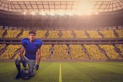 Immagine composita del ritratto del casco sicuro della tenuta del giocatore di football americano mentre mano sul ginocchio Fotografie Stock Libere da Diritti