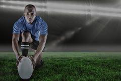 Immagine composita del ritratto del giocatore di rugby che si inginocchia e che tiene palla e 3d Fotografia Stock