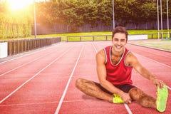 Immagine composita del ritratto dell'atleta maschio che allunga il suo tendine del ginocchio Fotografia Stock