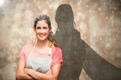 Immagine composita del ritratto della giovane donna sorridente con le armi attraversate Immagine Stock