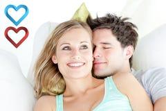 Immagine composita del ritratto di una coppia abbracciante che si siede su un sofà nel salone Immagine Stock Libera da Diritti