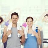 Immagine composita del ritratto di una coppia felice di misura con le bottiglie di acqua Fotografia Stock Libera da Diritti
