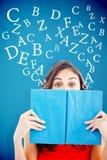 Immagine composita del ritratto di uno studente che si nasconde dietro un libro blu Fotografia Stock Libera da Diritti