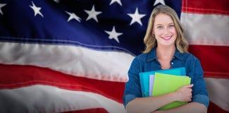 Immagine composita del taccuino e dell'archivio sorridenti della tenuta dello studente Immagini Stock Libere da Diritti