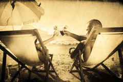 Immagine composita del tintinnio felice delle coppie i loro vetri mentre rilassandosi sui loro sdrai Fotografia Stock