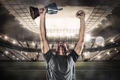 Immagine composita del trofeo felice della tenuta del giocatore di rugby Fotografia Stock Libera da Diritti