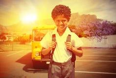 Immagine composita dell'allievo sveglio che sorride alla macchina fotografica in scuolabus Immagine Stock