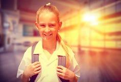 Immagine composita dell'allievo sveglio che sorride alla macchina fotografica in scuolabus Fotografia Stock