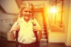 Immagine composita dell'allievo sveglio che sorride alla macchina fotografica in scuolabus Fotografie Stock