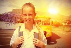 Immagine composita dell'allievo sveglio che sorride alla macchina fotografica in scuolabus Fotografia Stock Libera da Diritti