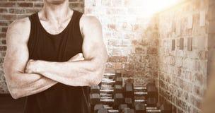 Immagine composita dell'atleta che sta con le armi attraversate Fotografie Stock