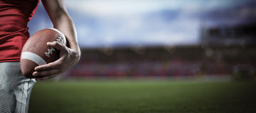 Immagine composita dell'immagine potata di football americano della tenuta dello sportivo Fotografia Stock Libera da Diritti
