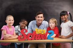Immagine composita dell'insegnante e degli allievi che sorridono alla macchina fotografica alla biblioteca Immagine Stock