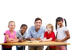 Immagine composita dell'insegnante e degli allievi che sorridono alla macchina fotografica alla biblioteca Fotografie Stock