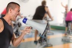 Immagine composita dell'istruttore maschio irritato che urla tramite il megafono Fotografie Stock