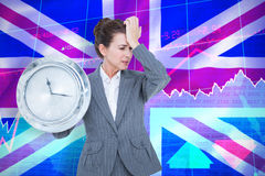 Immagine composita dell'orologio di parete della tenuta della donna di affari di ribaltamento Fotografie Stock Libere da Diritti