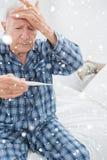 Immagine composita dell'uomo anziano che prende la sua temperatura Fotografia Stock