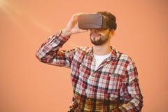 Immagine composita dell'uomo casuale dell'uomo che tiene i vetri virtuali su un fondo rosa Fotografie Stock Libere da Diritti