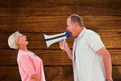 Immagine composita dell'uomo che grida al suo partner tramite il megafono Immagine Stock