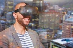 Immagine composita dell'uomo che indossa la cuffia avricolare virtuale del simulatore Immagine Stock Libera da Diritti