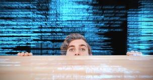 Immagine composita dell'uomo che si nasconde dietro lo scrittorio contro il fondo bianco Fotografia Stock