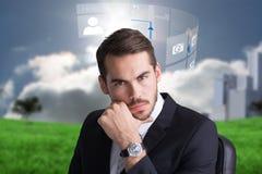 Immagine composita dell'uomo d'affari allegro che posa con la mano sul mento Fotografia Stock Libera da Diritti