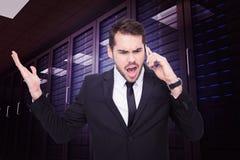 Immagine composita dell'uomo d'affari arrabbiato che gesturing sul telefono Fotografie Stock
